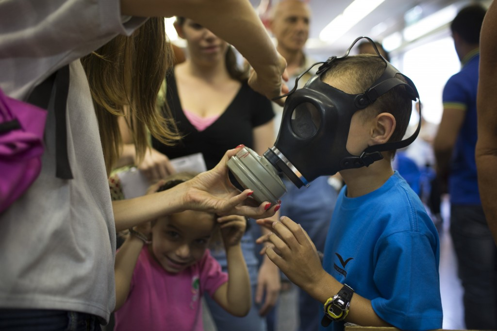Israeli child trying on a gas mask at a distribution center in Tel Aviv, Aug. 26. (Uriel Sinai/Getty Images)