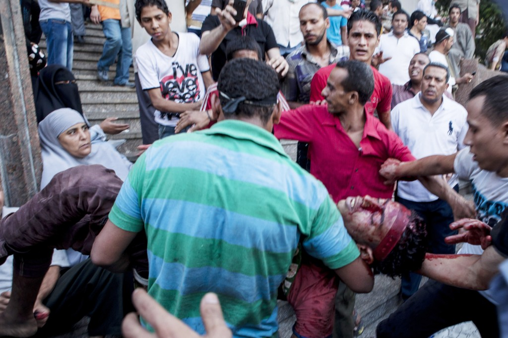 An injured supporter of deposed Egyptian President Mohamed Morsi is carried into the Fateh Mosque at Ramses Square in Cairo, Aug. 16, 2013. (Ed Giles/Getty)