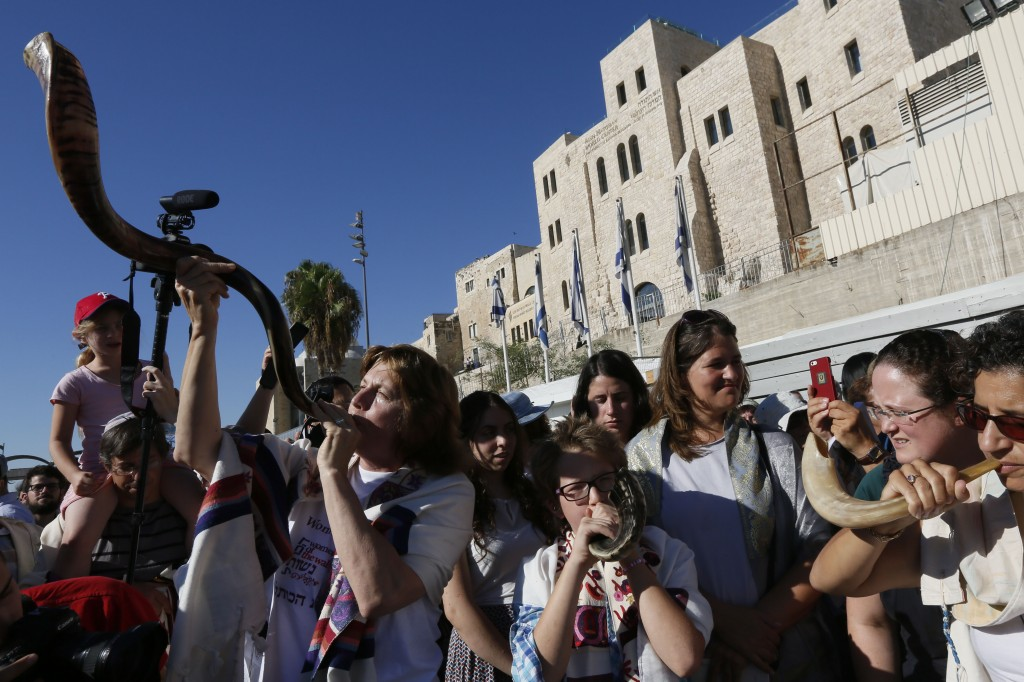Women of the Wall members blow the shofar at the back of the Western Wall Plaza during its monthly Rosh Chodesh service, Aug. 7, 2013. (Miriam Alster)