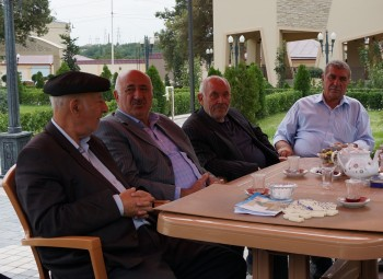 Yedidia Yehuda, right, sitting with Jewish lawmaker Yevda Abramov, second from left, in a Jewish tea house in Krasnaiya Sloboda, Aug. 22, 2013. (Cnaan Liphshiz)