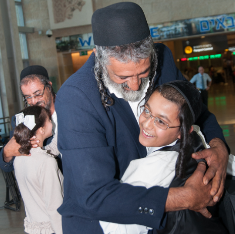 A father and son are reunited at Ben Gurion Airport following an airlift that brought 17 Yemeni Jews to Israel, Aug. 14, 2013. (The Jewish Agency Facebook)
