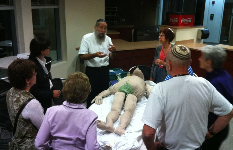Baruch Bloom, in white shirt, a board member of Kavod v'Nichum, demonstrates how to prepare a body for burial at the organization's 2012 conference in Los Angeles.