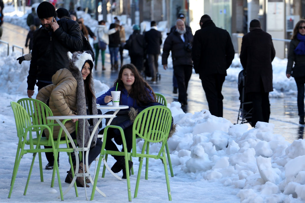 A cafe table is set up amid the snow on Jerusalem's Jaffa Road on Dec. 15, 2013. (Hadas Parush/Flash 90)