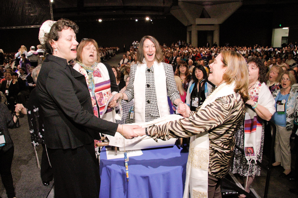 A group of women hold hands around the Torah during the Shabbat morning service at the Union for Reform Judaism's biennial conference in San Diego on Dec. 14, 2013. (URJ)