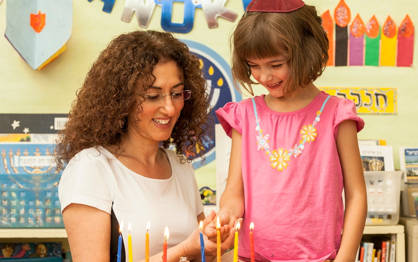Kindergarten teacher Nirit Yakov lighting a menorah with a student at Tehiyah Day School in California.  (Courtesy of Tehiyah Day School)