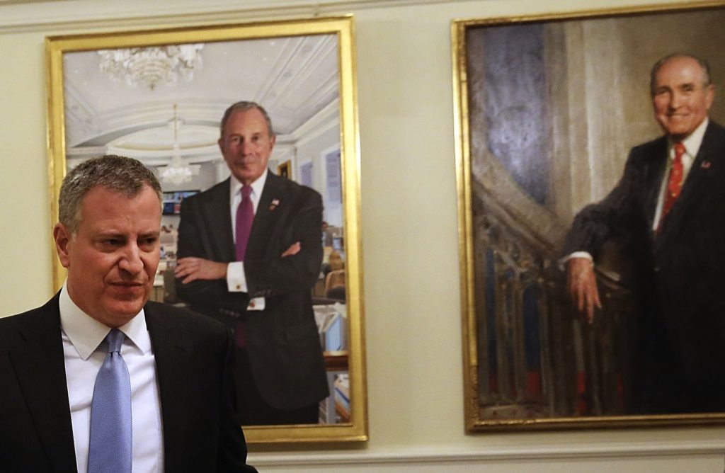 New York City Mayor Bill de Blasio, pictured here walking past portraits of his predecessors, said that defending Israel is part of his job description. (Spencer Platt/Getty Images)