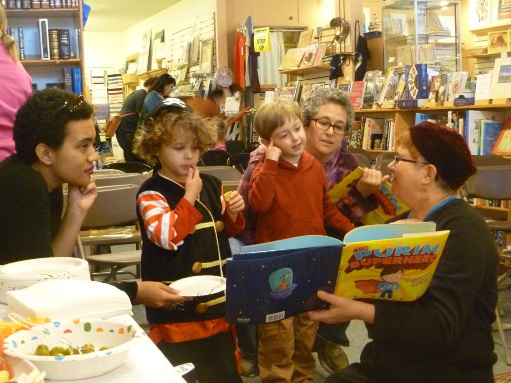"Author Elisabeth Kushner reads ""The Purim Superhero"" at a book-release party at Afikomen Judaica in Berkeley, Calif. (Keshet)"