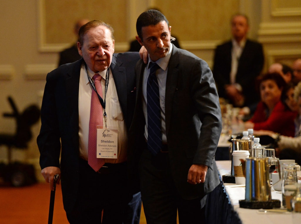 Sheldon Adelson (L) is escorted to his seat to listen to New Jersey Gov. Chris Christie speak during the Republican Jewish Coalition spring leadership meeting in Las Vegas. (Ethan Miller/Getty Images)