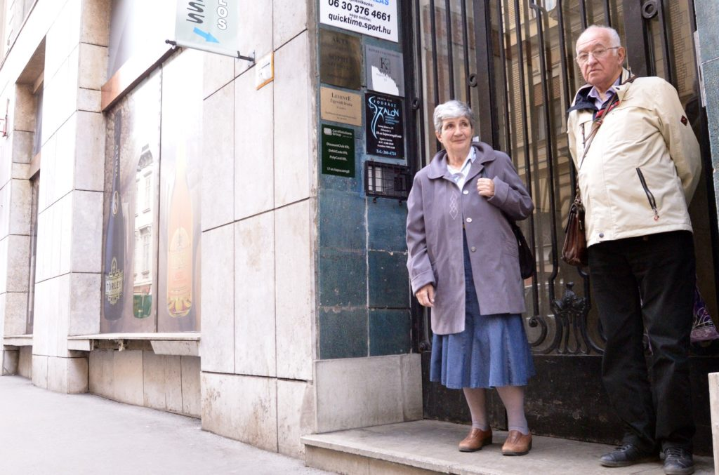 Holocaust survivors Agnes Horvath, left, and Andras Szasz in front of one of Budapest's 2,000 yellow star houses, March 27, 2014. (Cnaan Liphshiz)