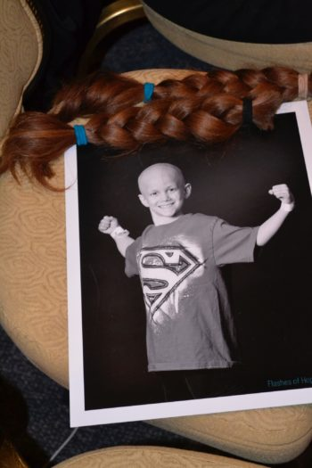 "Two newly shorn braids adorn a photo of Samuel Sommer, whose struggle with refractory acute myeloid leukemia inspired the Reform Rabbis Shave for the Brave campaign. Sommer, known to friends and family as ""Superman Sam,"" died in December at age 8. (Julie Pelc Adler)"