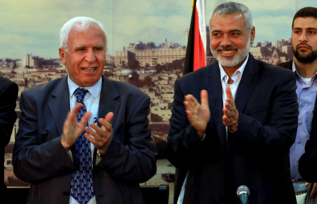 Palestinian Fatah delegation chief Azzam al-Ahmed (L) celebrates with Hamas prime minister in the Gaza Strip Ismail Haniya in Gaza City on April 23, 2014 after West Bank and Gaza Strip leaders agreed to form a unity government within five weeks. (Abed Rahim Khatib / Flash90)