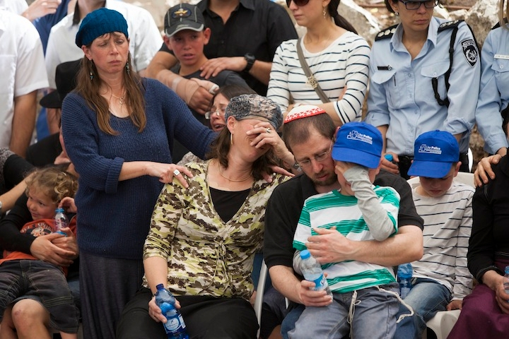 The family of Baruch Mizrahi, a senior Israeli police officer, mourns during his funeral at the military cemetery of Mount Herzl in Jerusalem on April 16, 2014. Mizrahi was shot by Palestinians on April 14 near the West Bank city of Hebron while driving with his wife and young son, who were also injured in the attack, as they were on their way to a Passover seder. (Yonatan Sindel/Flash90)