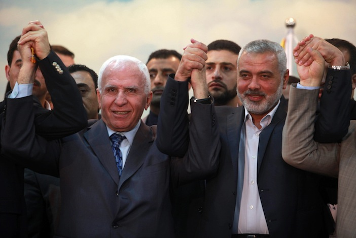 Head of the Hamas government Ismail Haniyeh and senior Fatah official Azzam Al-Ahmed attend a news conference as they announce a reconciliation agreement in Gaza City on April 23, 2014. (Abed Rahim Khatib/Flash90)