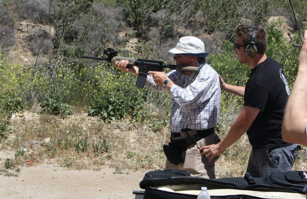 Itamar Gelbman adjusts Les Hajnal's stance as he fires an AR15 rifle, during a shooting class for American Children of Jewish Holocaust Survivors. (Anthony Weiss)