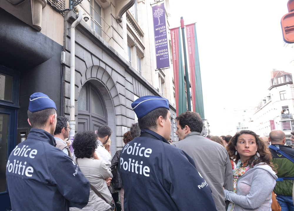 Police guarding participants of a silent vigil on May 25 outside Brussels' Jewish museum. (Cnaan Liphshiz/JTA)