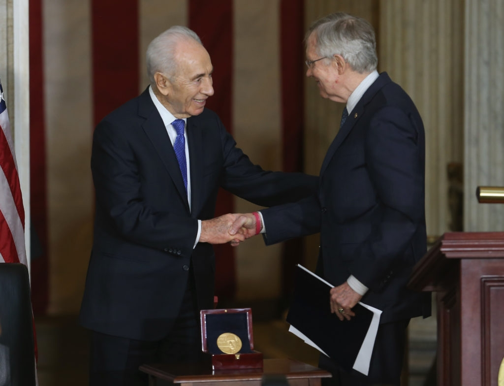 Israeli President Shimon Peres (L) shakes hands with Senate Majority Leader Harry Reid (D-NV) during a Congressional Gold Medal ceremony at the U.S. Capitol, June 26, 2014 in Washington, D.C. (Mark Wilson/Getty Images)