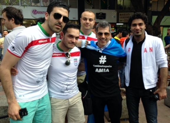 "Fabio Kornblau, a former member of the AMIA Jewish center board, posing with Iranian soccer fans before the Argentina-Iran match at the stadium in Belo Horizonte, Brazil, while wearing a T-shirt with the ""One minute for AMIA"" motto in Spanish. (Courtesy Fabio Kornblau)"
