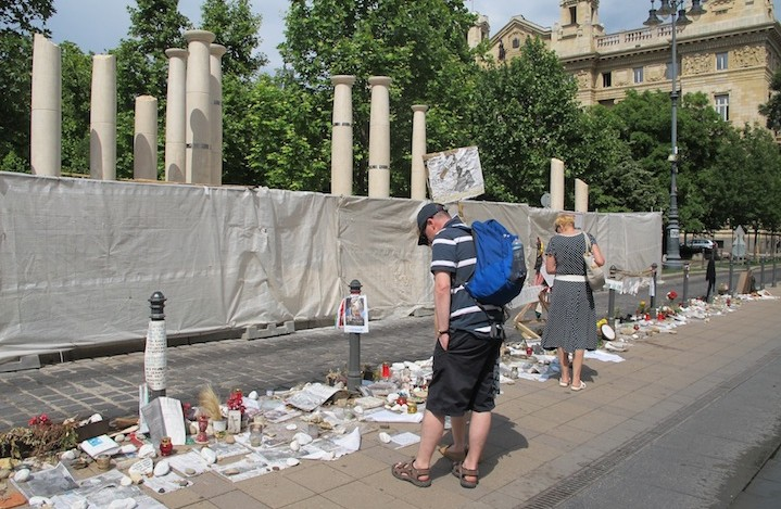 Passersby look at the Holocaust-related and other memorabilia left by citizens protesting the monument to the 1944 German occupation, under construction behind sheeting across the street in downtown Budapest. (Ruth Ellen Gruber)