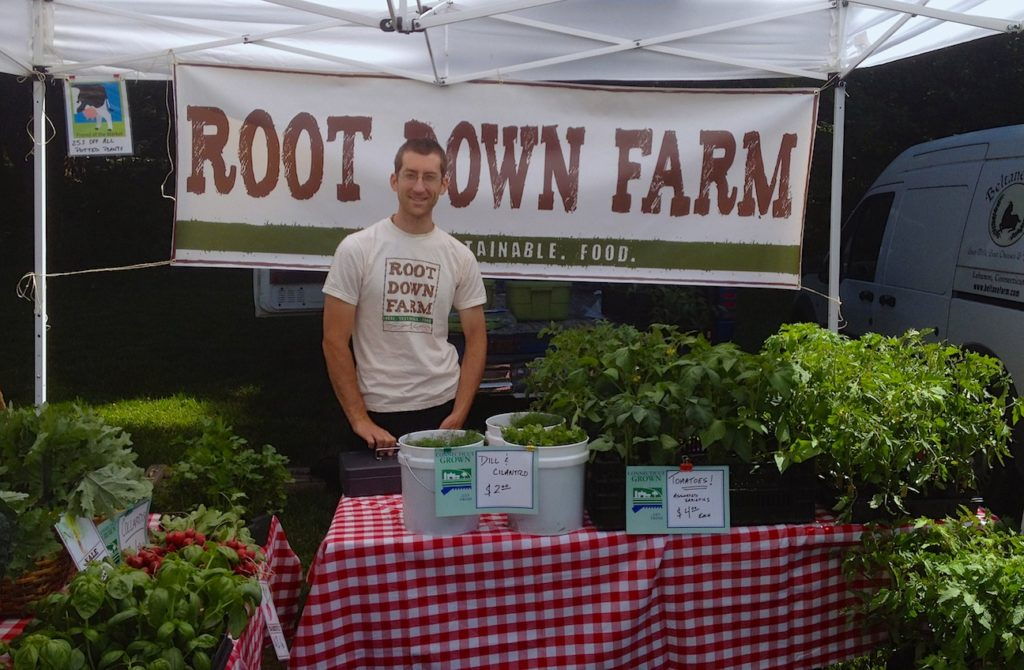 Farmer Fred Grave staffs the Root Down Farm stand at the Coventry Regional Farmers Market.
