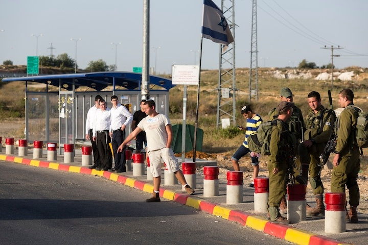 Israeli soldiers guard near where Jewish settlers hitchhike at the Gush Etzion junction in the West Bank, June 16, 2014. (FLASH90)