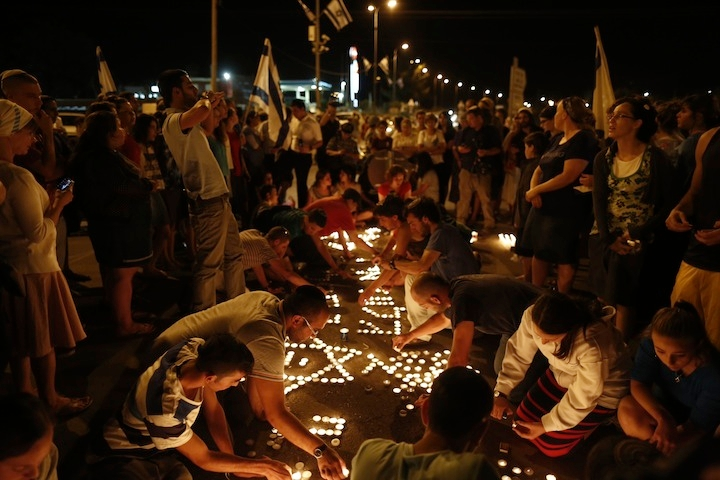 At the hitchhiking spot in the West Bank where three teenagers -- Eyal Yifrach, Naftali Fraenkel and Gilad Sha'ar -- were abducted, Israelis light memorial candles after the discovery of their bodies, June 30, 2014. (Yonatan Sindel/Flash 90)