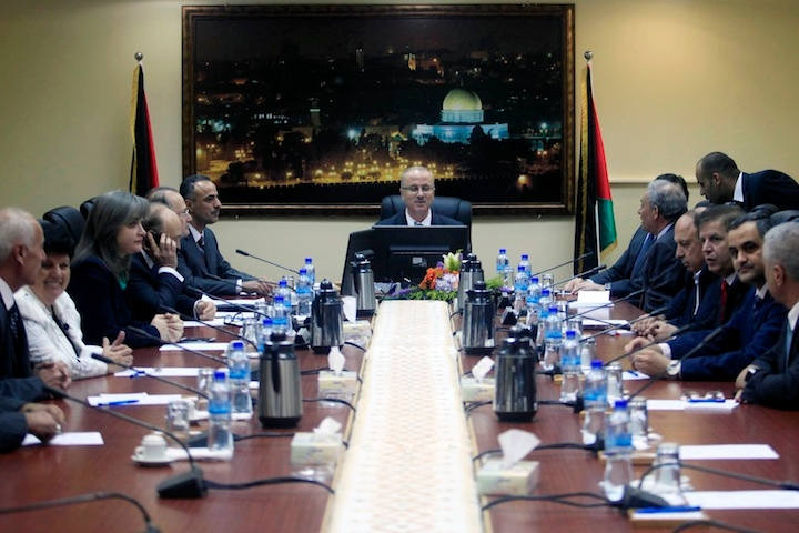 Prime Minister Rami Al-Hamdallah, at head of table, attending his first meeting of the new unity government Cabinet in the West Bank city of Ramallah, June 3, 2014. (Issam Rimawi/Flash90)