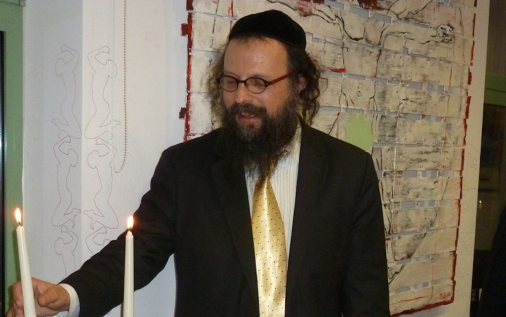 Former Krakow Chief Rabbi Boaz Pash lighting a candle for Hannukah in 2010. (Shavei Israel)