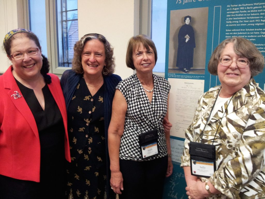Rabbis Jacqueline Tabick, Amy Eilberg, Sandy Eisenberg Sasso and Sally Priesand stand with a photo of Rabbi Regina Jonas at Centrum Judaica in Berlin, July 22, 2014. (Toby Axelrod)
