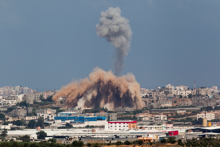 Smoke and debris rise from a site in Gaza after an Israeli airstrike, July 9, 2014. (Yonatan Sindel/Flash90)