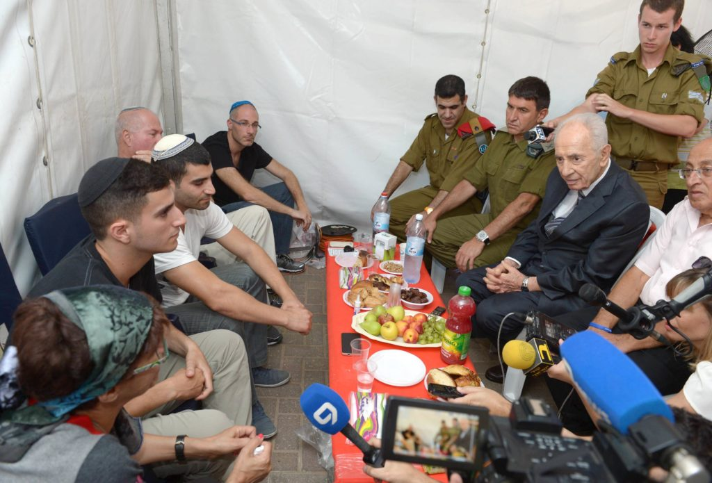 Israeli President Shimon Peres paying a shiva visit for one of the Israeli soldiers killed in Gaza, July 21, 2014. (Mark Neiman/Israel Government Press Office