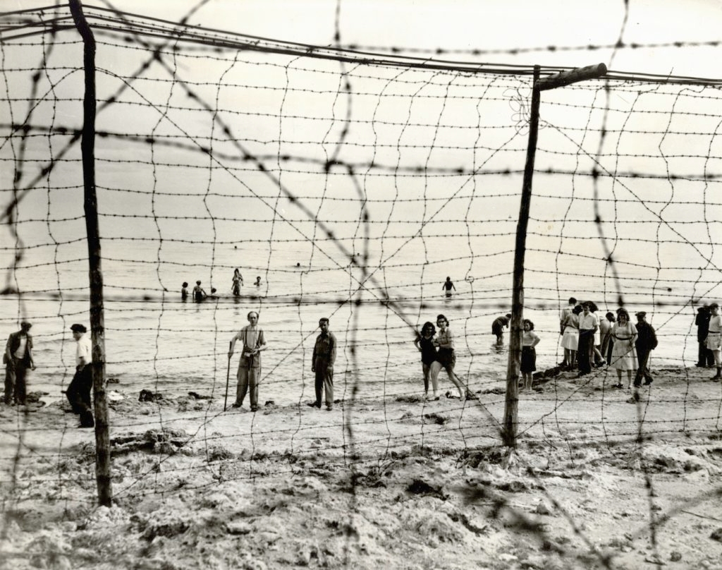A group of Jewish refugees in a British detention camp in Cyprus swim in the Mediterranean Sea behind a barbed wire fence that surrounds the camp, 1946. The refugees were permitted use of the beach from 10 a.m. to 5 p.m. daily. (Courtesy JDC Archives)