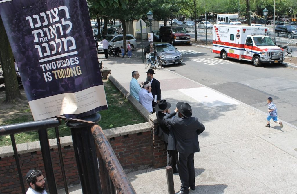 "A placard outside a Chabad yeshiva in Crown Heights adjacent to the Lubavitcher rebbe's onetime office in Brooklyn is a sign of the messianism that still pervades the movement. ""It is our will to see our king,"" the placard says in Hebrew, and then in English,""Two decades is too long,"" June 30, 2014. (Uriel Heilman/JTA)"