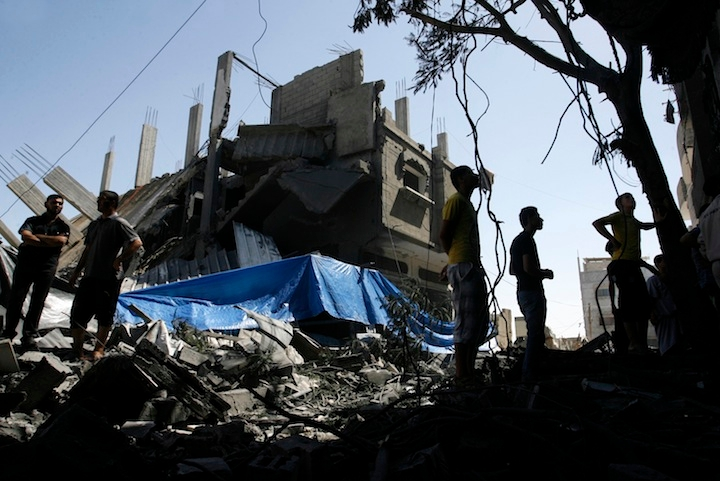 Palestinians walking among the rubble of a destroyed house following an Israeli missile strike, in Rafah, in the southern Gaza Strip, July 14, 2014. (Abed Rahim Khatib/Flash 90)