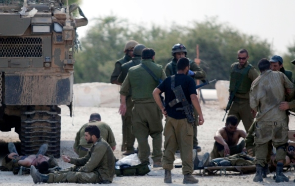 Israeli soldiers milling around the wounded from combat in the Shejaiya neighborhood of Gaza City, July 20, 2014. (Flash90)
