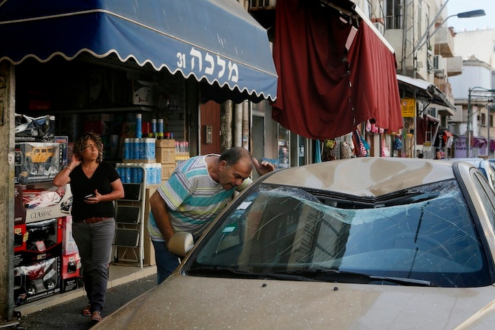 Israelis looking on at the site where remains of one of the rockets fired from Gaza into Israel that was intercepted by the Iron Dome fell in South Tel Aviv. July 10, 2014. (Miriam Alster/FLASH90)