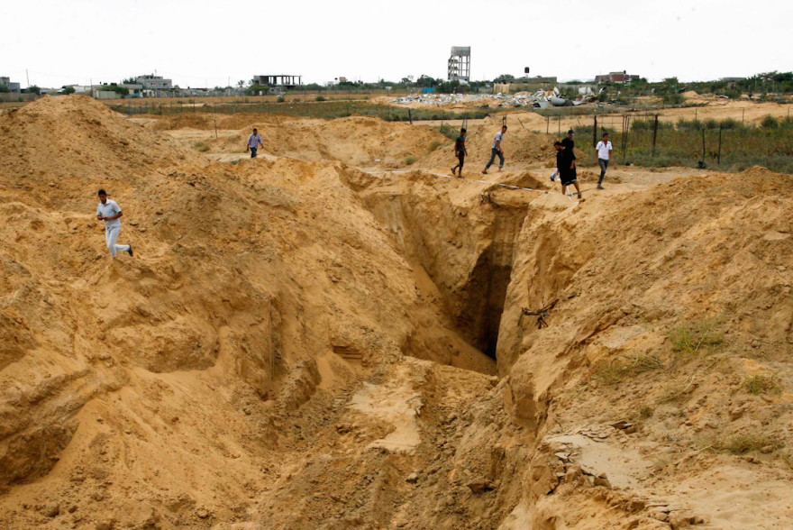Palestinian men look at what used to be a tunnel leading from the Gaza Strip into Israel, in the area of Rafah in the southern Gaza Strip, on Aug.  5,  2014, after a 72-hour truce agreed by Israel and Hamas went into effect. (Abed Rahim Khatib/Flash90)