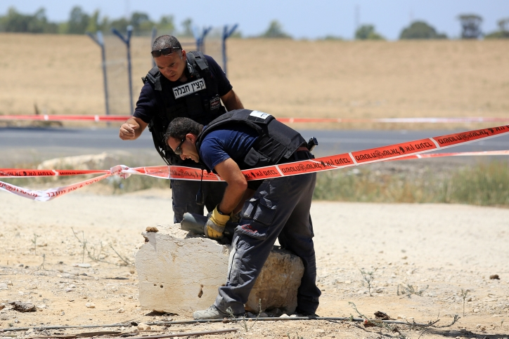 Police sappers inspect part of a rocket fired into Israel from Gaza after Hamas renewed its rocket launches following the expiration of a 72-hour cease-fire, Aug. 8, 2014. The Israeli army responded with airstrikes in Gaza. (Edi Israel/Flash90)