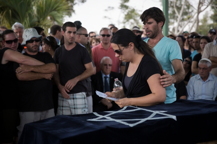 Gila Trigerman is comforted by her husband, Doron, while speaking at the funeral of their 4-year-old son, Daniel, at the Hevel Shalom Cemetery in southern Israel, Aug. 24, 2014. (Hadas Parush/Flash90)