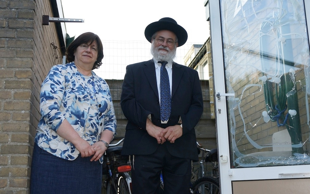Rabbi Binyomin Jacobs and his wife, Bluma, by the glass window of their home damaged in an attack on July 17, 2014. (Cnaan Liphshiz)