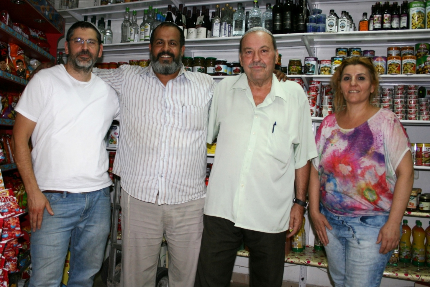 Solomon Cohen, second from right, and his daughter, Penina, at Cohen's store in Sderot with Avichai Amusi, left, of Mercaz Hachesed and Yedidya Rosenberg of Leket Israel, Aug. 3, 2014. (Guy Yehoshua)