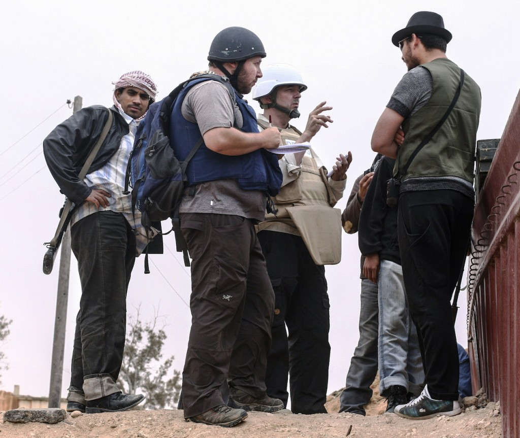 In this handout image made available by the photographer, American journalist Steven Sotloff (center with black helmet) talks to Libyan rebels on the Al Dafniya front line, 25 km west of Misrata, June 2, 2011.  Sotloff was kidnapped in August 2013 near Aleppo, Syria.  (Etienne de Malglaive via Getty Images)