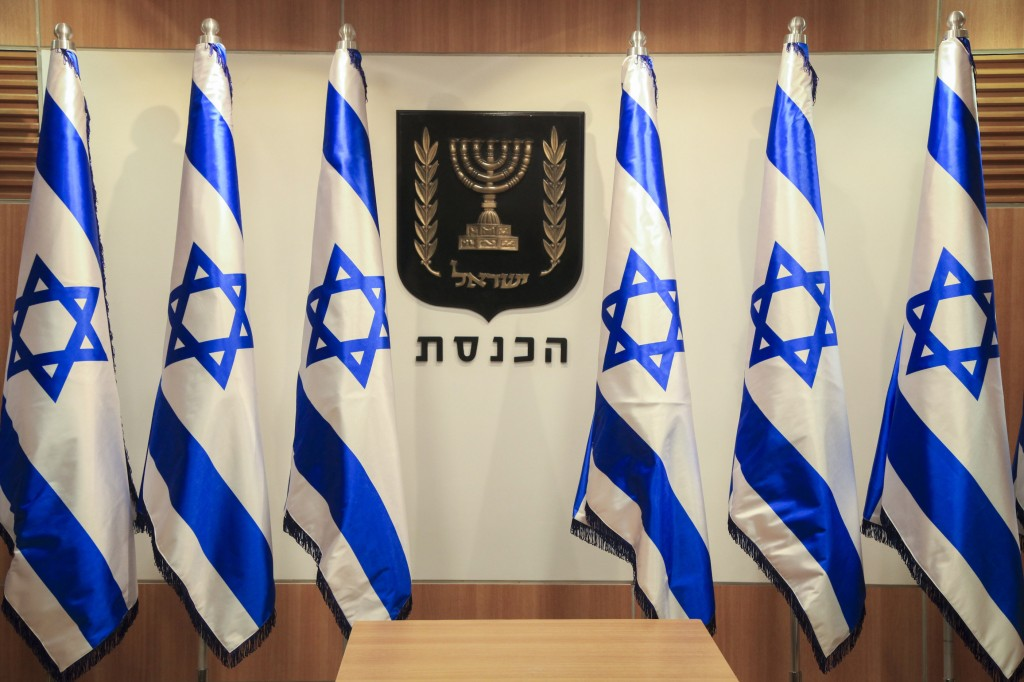 Israeli flags standing next to the Israeli state symbol in the Knesset, Nov. 6, 2014. (Nati Shohat/Flash90)