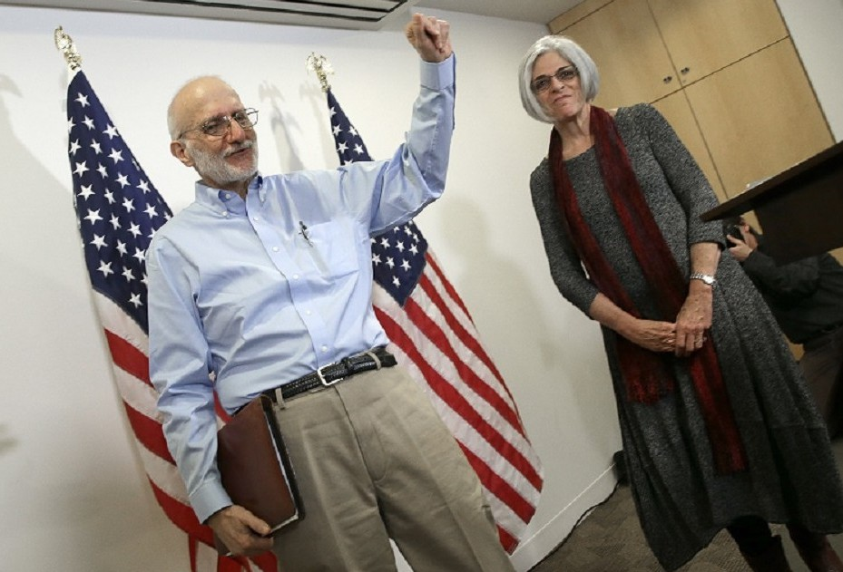 Alan Gross, recently released by Cuban authorities, waves after concluding his remarks with his wife Judy (R) at a press conference at his lawyer's office shortly after arriving in the United States, Dec. 17, 2014 in Washington, DC.  (Photo by Win McNamee/Getty Images)
