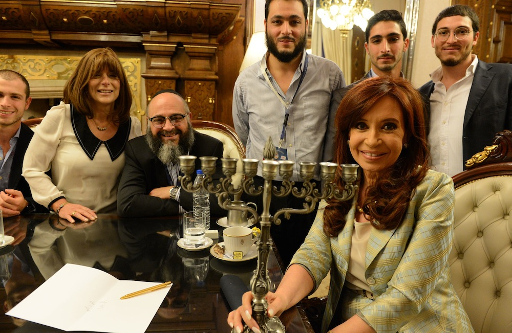 Argentine President Christina Fernandez lighting Hannukah candles with the family of Shlomo and Nechama Tawil, whose son became the first Jewish boy adopted under a law intended to counteract an old Argentine legend.