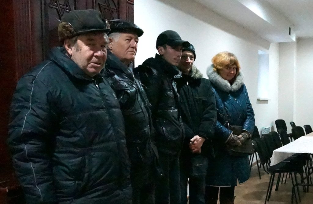 Members of Lugansk's Jewish community in front of their synagogue's Torah Ark, Dec. 11, 2014. (Cnaan Liphshiz/JTA)
