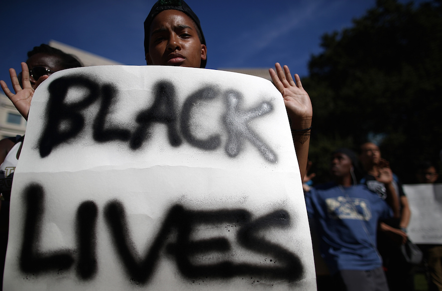 A demonstrator holding a sign during a moment of silence for victims of police brutality, in Oakland, California, Aug. 14, 2014. (Justin Sullivan/Getty Images)