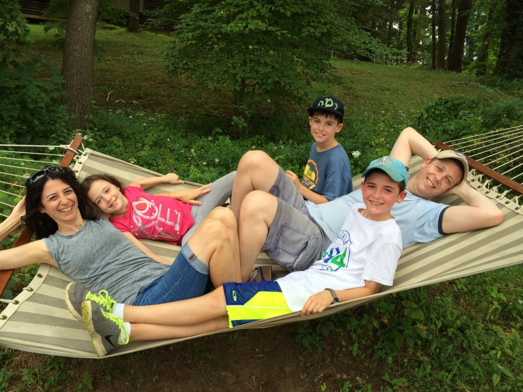 Liz and Dan Spevack with children Ayelet, Noam and Eytan, on a hammock at Ramah Berkshires. The Spevacks, who met at Ramah Berkshires, are among the approximately 700 couples who met at Ramah camps. Dan Spevack's parents also met at Ramah Berkshires, and all three children attend Ramah camps. (Courtesy of Liz Spevack)