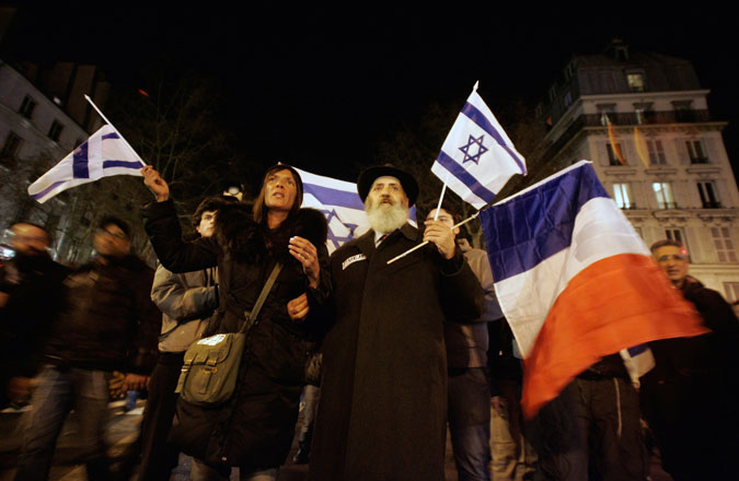 Members of the Jewish community demonstrate on Place de la Bastille as they attend a silent march to pay tribute to the victims of the Toulouse school shooting, during a night time vigil on March 19, 2012. (Franck Prevel/Getty Images)