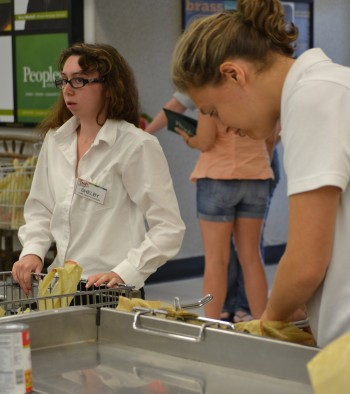 Atzmayim participants Rachel Palmer (right) and Shelby Marcus bag groceries at Trig's, a supermarket in Eagle River, Wis. (Courtesy of Ramah Wisconsin)
