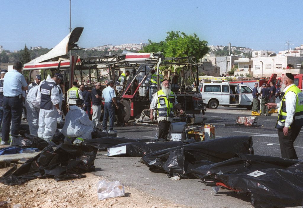 Israeli rescue workers tend to victims' bodies from the scene of a Palestinian suicide bombing on a passenger bus in Jerusalem June 18, 2002. (Yossi Zamir/Flash 90)